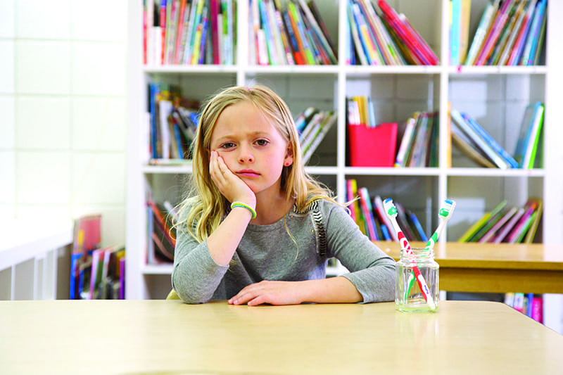 bored looking girl sitting at a desk