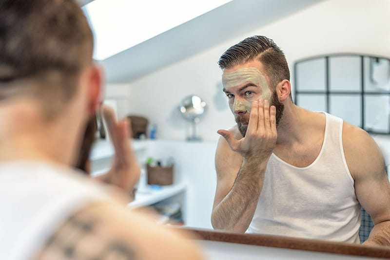 Just for Men - man putting on mud mask in a bathroom