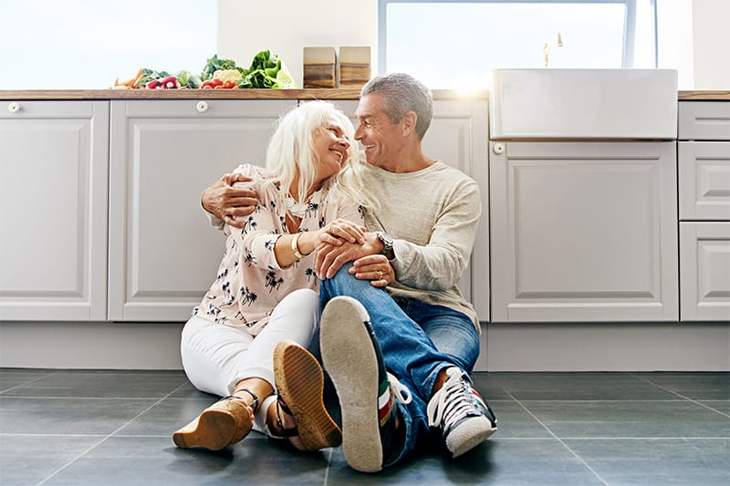 Man and woman cuddling while sitting in a kitchen