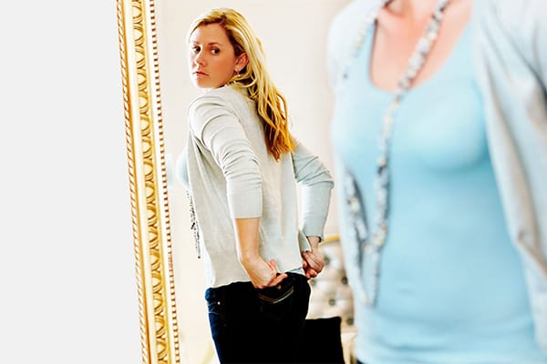Woman looking at her back side in a mirror