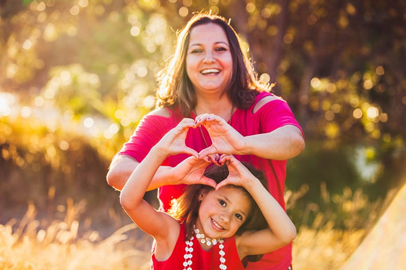 Mom and daughter smiling while making hearts with their hands