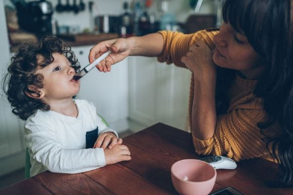 Woman gives toddler liquid medication with a mouth syringe
