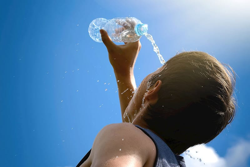 Person pouring water from a bottle on their face on a sunny day