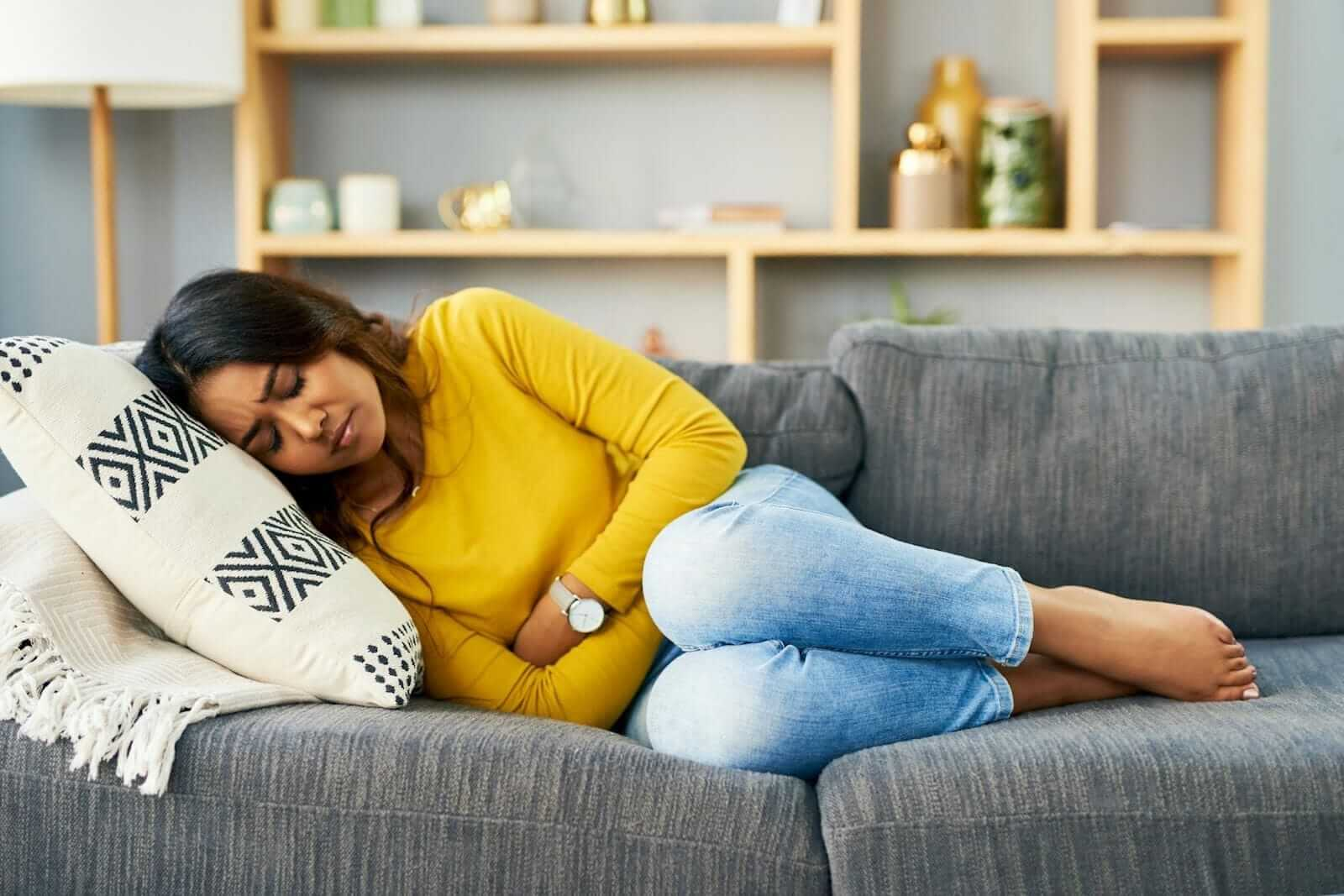 Woman holds arms over her stomach in pain laying on couch