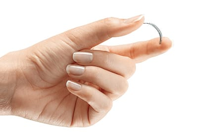 Hand holding the Essure® device