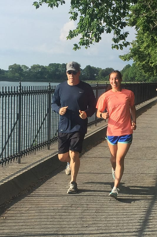 Photo of Greg Gaumer and his daughter running near a lake