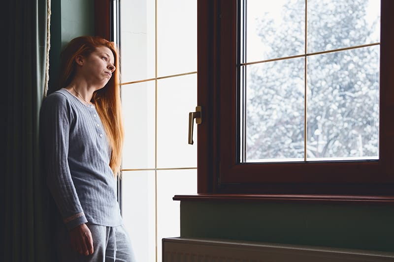 Depressed looking woman looking out the window at snow