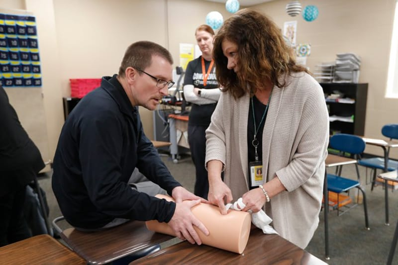 Dr. Richard Sidwell helping woman practice putting pressure on a wound on a dummy leg