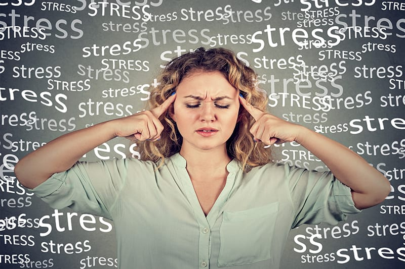 Woman closing her eyes with the words stress floating around her