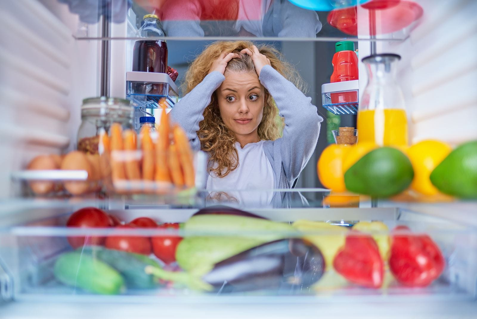 woman stands in front of a fridge filled with vegetables