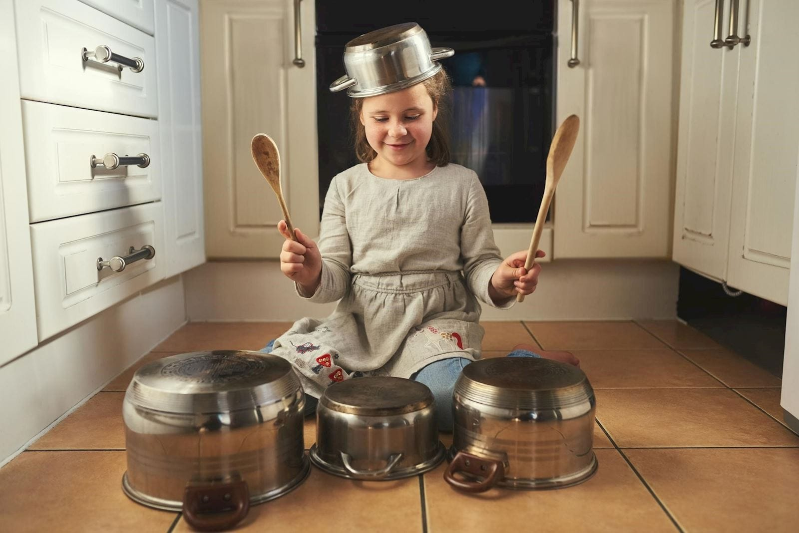 Child with ADHD banging on pots and pans with wooden spoons