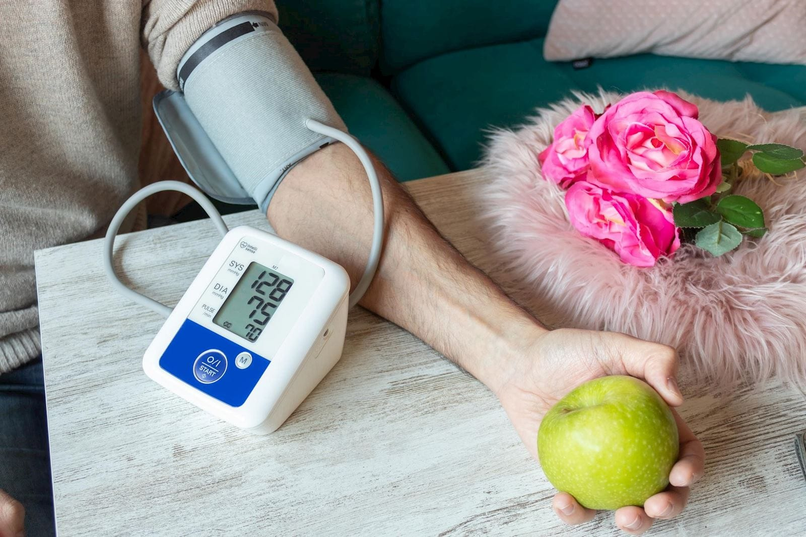 Man takes blood pressure with a cuff while holding an apple in his hand