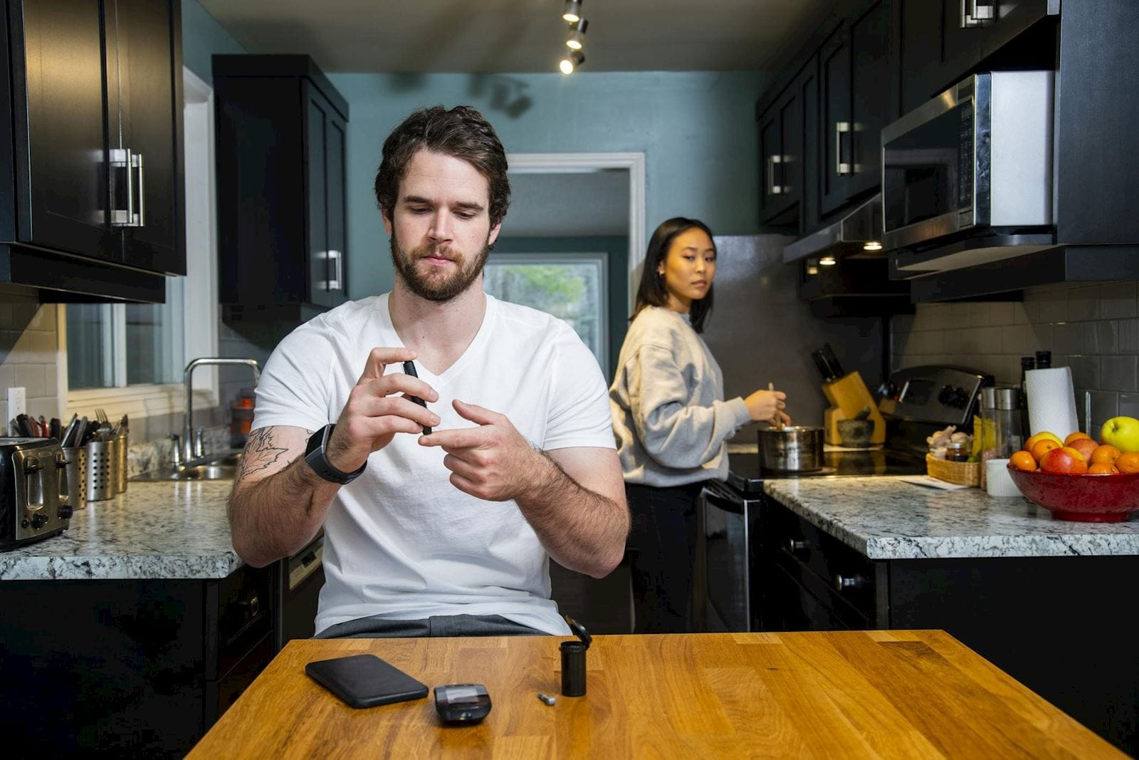 Man with diabetes checks his blood sugar with a finger prick while sitting in his kitchen