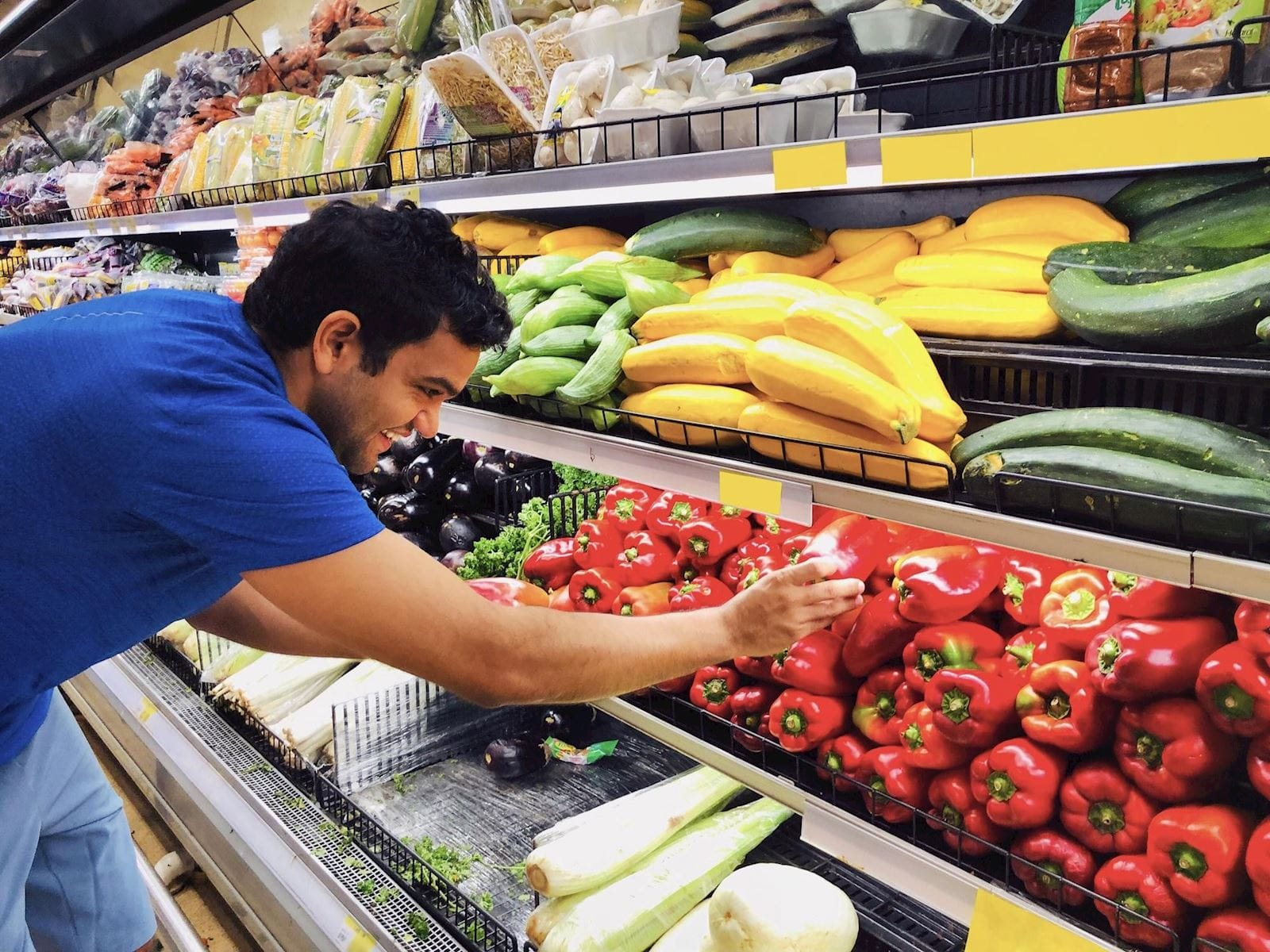 man selects red pepper from produce section at grocery store