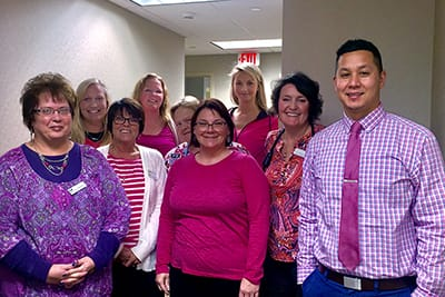 Smiling group of Iowa Clinic staff wearing pink