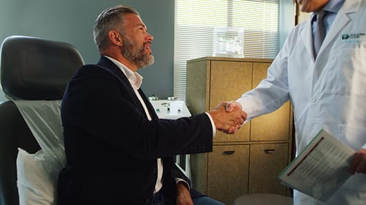 man sitting and shaking hands with Medical Spa physician